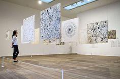 Employee observes Mira Schendel's works at Tate Modern