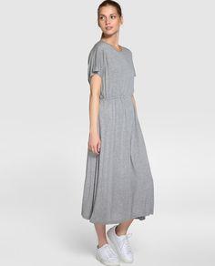 Vestido largo, en color gris liso. Tiene manga corta, escote redondo y cinturilla elástica.