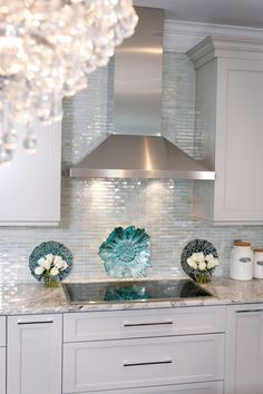 Iridescent glass tile by Lunada Bay. Stainless hood with taupe cabinets.  Color looks good.