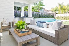 Lovely patio features a vaulted ceiling alongside a wicker sofa facing a weathered teak coffee table.