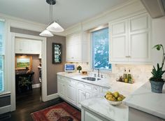 Small white kitchen with great marble counters. Love the greige wall paint, and the rug really warms everything up.