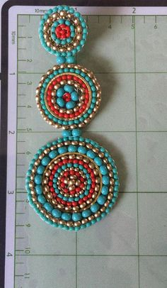 Beaded triple disc seed bead post earrings. If you like bold, statement jewelry, you will love these gorgeous earrings made with ruby, turquoise and antiqued gold seed beads. Each bead is individually expertly woven to make these beautiful earrings. The post earwires are hypo allergenic