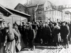 Survivors of Auschwitz leaving the camp at the end of World War II, Poland, February 1945. Above them is the German slogan 'Arbeit macht frei' ('Work makes one free'). Photo taken by a Russian photographer during the making of a film about liberation of the camp. (Photo by Galerie Bilderwelt/Getty Images)