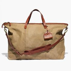 """You asked for it: We sized up our signature ruggedly cool carryall so it's perfect for a weekend away (or even just a crosstown trek). Trimmed with low-key leather accents, this version comes complete with a handy removable shoulder strap, a secure top zip and a cool little luggage tag. Feel free to check it on the plane—the durable waxed canvas looks better and better the more beat up it gets. <ul><li>Canvas, leather.</li><li>Zip closure.</li><li>Interior pocket.</li><li>17 3/4"""" shoulder…"""