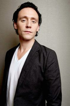 """Tom Hiddleston giving you that """"come here"""" look while trying not to smile."""