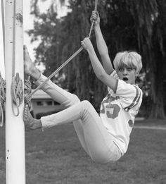 American dancer and dance instructor and future actress Goldie Hawn in jeans and a football jersey clowns about as she hangs from a flagpole...