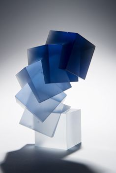 German glass artist Heike Brachlow finds inspiration in architecture and geometry, creating cast glass sculptures that rely heavily on their shape, which is often that of a cylinder or cube. Works in her Theme and Variation series seem to impossibly balance as they subtly curve upwards, individual c