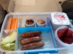Breakfast sausages, avocado, carrot sticks, almonds, hummus, strawberries and yogurt.