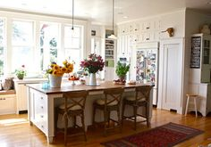 Gorgeous, homely kitchen. Love everything about it- the long windows, persian rug, white with splashes of colour. Warmth!
