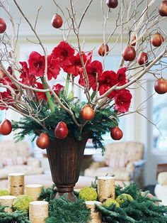 Dangling Style:   Make a statement with a large flower arrangement surrounded by smaller candles. This dramatic display includes amaryllis plants, evergreen boughs, and small red pears hanging from ordinary branches.