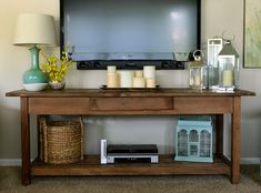 Wall mounted TV with console table underneath: I really like how they've organized the console table to be functional and decorative.