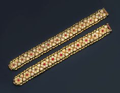 A PAIR OF DIAMOND, RUBY AND ENAMEL BRACELETS Of foliate design, each comprising a series of table-cut diamond flower-heads with foiled ruby centres to triple-stone intersections and beaded borders, the reverse decorated with polychrome enamel of similar design, Jaipur, mid 19th century, each 18.0cm. long