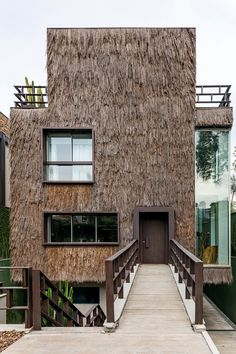 the brazilian design-duo's first residential project features a shaggy façade made of 'piassava' and simultaneously functions as a tropical heat shield.