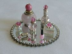 These beautiful miniature 8 piece vanity sets are all handmade using various combinations of glass, metal, stone, bone, crystal and semiprecious elements. Each set includes 5 bottles of various sizes, one tube of lipstick and one bottle of nail polish along with a gorgeous jeweled mirror tray for display. Small parts, not suitable for children. For display only.