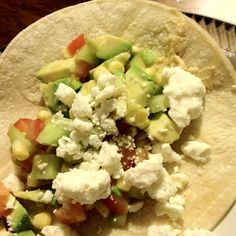 Vegetarian Greek Taco- corn tortilla with hummus topped with a mixture of corn, avocado, tomato and cucumber topped with feta! Rave reviews at home!