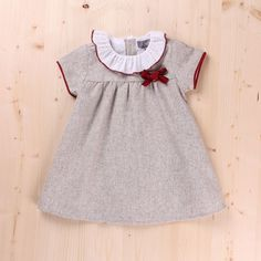 Vestido bebé liso gris con cuello volante liso blanco acabado con hilo granate, corte al pecho y lazo en terciopelo granate. Vivo granate en la manga.