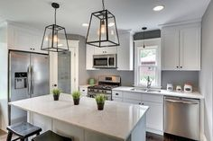 White and gray kitchen features a corner frosted glass pantry door placed next to an under cabinet ...