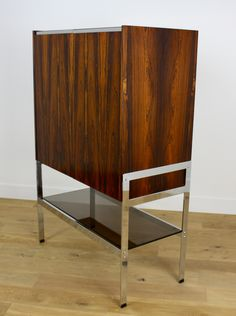 Mid Century Modern Design Dry Bar. Stunning Rosewood and Chrome Dry Bar, Designed by Richard Young for Merrow Associates. Beautiful Rosewood Cabinet raised on high quality flat Chrome frame over a smoked glass shelf. Contrasting Ash interior with two glass shelves over pull out serving shelf and two drawers. 138 Cm h 91.5 Cm w 46 cm d British C 1970