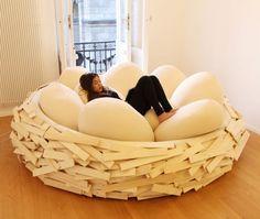 """O delicioso sofá """"The Giant BirdNest"""" criado pela OGE Design. O ninho de madeira é cheio de pufs em forma de ovo e permite sentar em diferentes posições."""