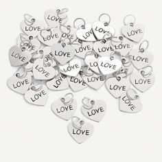 """Heart-Shaped """"Love"""" Charms. Share a symbol of your love! Give these charms out after your wedding reception or party. Silvertone metal Heart-Shaped """"Love"""" Charms have """"Love"""" etched into the center. They can be attached to key chains and gift bags. (3 dozen per unit) 1/2"""" © OTC"""