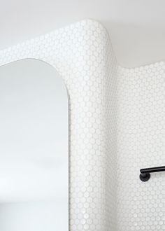 curved corner covered in white penny tile