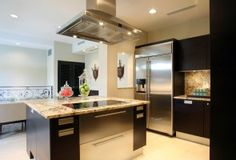 The granite countered kitchen is fully furnished with GE Monogram appliances
