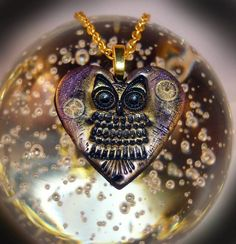 """Nocturne Owl Pendant - Heart shaped hand crafted polymer clay pendant with an embossed owl design and vintage watch parts, in shimmering shades of metallic gold and purple. Size - 4cm x 4cm. On a gold plated chain, length 18"""" - 20"""" - With a small golden wing at the end of the extender chain. Price -  £14.99"""