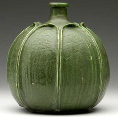 """GRUEBY:  Gourd-shaped vase with tooled and applied full-height ribbed leaves, covered in a superior feathered matte green glaze. (Extremely rare, one of Grueby's most important forms.) Professional restoration to small chip at rim and to a couple of leaf tips, several minor glaze nicks to leaf edges. Stamped GRUEBY. 9 1/4"""" x 8 1/2"""""""