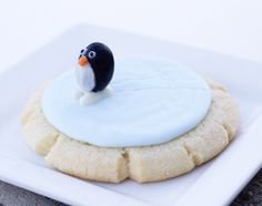 Ice Skating Penguin Cookies | The penguins are made from black licorice jelly beans (or Junior Mints) with white chocolate eyes, bellies and skates, and orange Nerd candies for the itty bitty beaks.