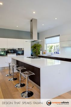"""Dark oak cabinetry from Aran Cucine's """"Erika"""" collection, white glossy cabinets from the """"Doga"""" collection. Folding wall cabinets integrated with under-cabinet lighting. Caesarstone countertop in Blizzard."""