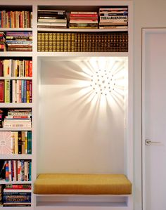 Over the built-in bench in the upstairs library is a Sputnik-like sconce from Jonathan Adler.