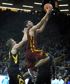 Iowa State forward Georges Niang lays the ball in past Iowa's Mike Gesell, left, and Peter Jok on Friday. Photo by Nirmalendu Majumdar/Ames Tribune