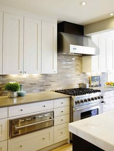 Nice cabinetry and back-splash....why the different coloured knobs?...or are they simply reflecting the dark colour of the island opposite..something to consider when selecting cabinet hardware...