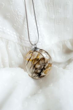Resin pendant gold flakes and real feathers. Stainless steel and resin combination for a luxury and original jewelry. Handmade by PAGANE uniques