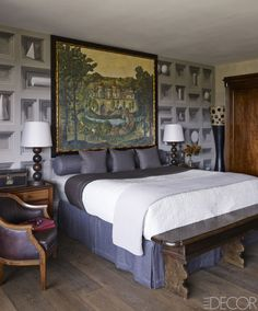 In the master bedroom, an 1880s French painting hangs above a bed dressed with custom bedding by Mirabel Slabbinck, with a bed skirt and bolsters in a Jasper fabric; the armchair is upholstered in a Holly Hunt leather, the circa-1900 English chest was originally used on the White Star cruise line, and the wall mural is by Tamara Codor.    - ELLEDecor.com