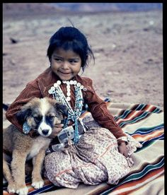 Little Navajo Indian Girl. A sweet child of the Navajos holding on to her pet dog. She wears the rich jewelry and sewed on dimes which constitutes wealth. among this southwestern Indian tribe. Around 1943