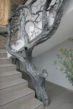 Tree railing / bannister in silver, growing beside staircase.