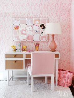Pink girl's bedroom with abstract pink wallpapered walls and ceilings framing a Mid-Century style desk topped with a vintage pink lamp and Set of 2 CB2 Gold Pig Bookends below a pink and white grid patterned memo board.