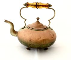 Antique English Tea kettle made of copper with an amber glass handle. Verdigris patina with a few small dents.
