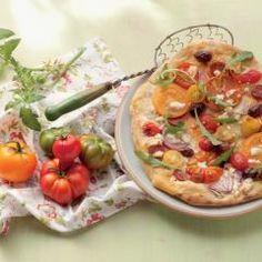 Frisch aus dem Garten oder vom Balkon, direkt auf den leckeren Flammkuchen-Teig: Fruchtige Tomaten sind die Stars dieses Rezepts. Der Flammkuchen ist außerdem pikant belegt mit Feta, Oliven und frischem Rucola.