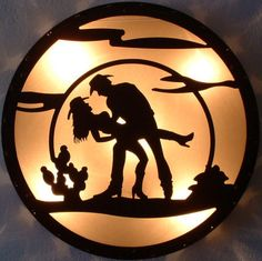 "24"" Diameter large wall sconce constructed of rustic steel with soft shade panels, illuminating a sillouette of a cowboy and his woman. 2 60 watt fixtures."