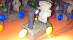Tiny teddy riding a scooter. An adaptation to the tiny teddies driving a car) Ingredients: Tiny teddies, Milky Way (fun size), Smarties, Chocolate Mint Sticks. Melt chocolate to stick all elements onto milky way
