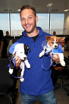 Tom Hardy poses for a photo with two puppies in support of Battersea Dogs and Cats Home at the BGC Annual Global Charity Day at Canary Wharf on September 12, 2016 in London, England.
