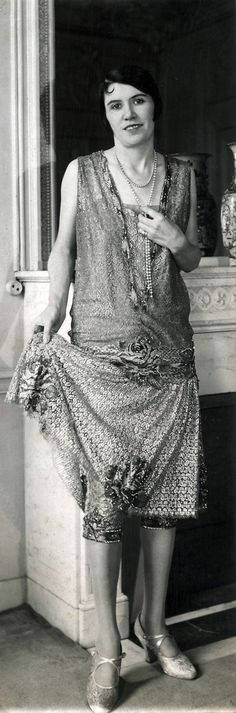 Women's Fashion. Model shows the Parisian fashion winter of 1926. She wears a sleeveless evening gown, richly decorated with lace and floral motifs, and under the skirt a breeches with piping. As jewelery she has a long chain around the neck. The creation of fashion Philippe et Gaston. Paris, France, 1926.