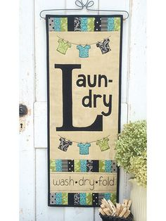 "Add a little splash of fun to your laundry room!   Easy piecing, applique and a bit of embroidery make this banner a whimsical and bright project! Even though laundry seems endless, this project can be done in no time. Display it with pride in your laundry room to put a smile on your face every time you walk in. Finished size is 11 1/2"" x 30""."