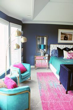 Bright Pink, Turquoise, and Navy Master Bedroom Makeover | Jennifer Allwood Home | With new bold bedding, this glam chic master bedroom makeover makes such a statement with navy painted walls, gold lighting, and a white modern headboard. #glamchic #masterbedroom #pinkdecor