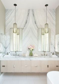 A glamorous bathroom design in white, cream, gray, and gold featuring marble walls and countertops, a modern creamy to blush pink vanity, tall mirrors and pendant lights - Chic Bathroom Ideas & Decor - lonny.com