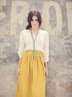 3/4 sleeves, mustard skirt, stranded turquoise necklace.