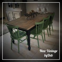 Eettafel met mat zwarte bolpoten en 4 salie groene houten keukenstoelen