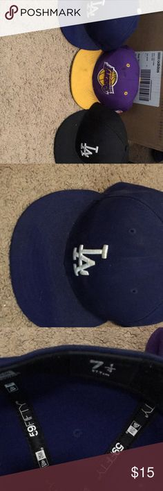 3 hats 2 LA dodger and A Los Angeles lakers hat 3 hats 2 LA 1 black/white 1 blue/white and a purple and yellow Los Angeles lakers hat. The blue/white LA hat and the Los Angeles laker hate are both size 7 1/4 and the black/white dodger hate is a 6 5/8 both dodger and are in good condition but dirty and the lakers hat is used a bit more. Selling as is. Can be cleaned. New Era Accessories Hats